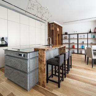 Выдающиеся фото от архитекторов и дизайнеров интерьера: кухня-гостиная в современном стиле с черной техникой, островом, плоскими фасадами, белыми фасадами, столешницей из дерева, паркетным полом среднего тона и коричневым полом