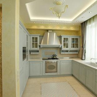 Inredning av ett avskilt, mellanstort u-kök, med en undermonterad diskho, luckor med upphöjd panel, turkosa skåp, bänkskiva i koppar, grått stänkskydd, stänkskydd i mosaik, rostfria vitvaror, klinkergolv i porslin och turkost golv