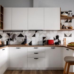 На фото: п-образная кухня в скандинавском стиле с плоскими фасадами, белыми фасадами, деревянной столешницей, разноцветным фартуком, черной техникой, светлым паркетным полом и полуостровом