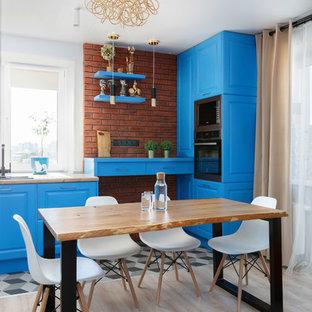 Ejemplo de cocina en U, actual, abierta, sin isla, con fregadero encastrado, armarios con paneles con relieve, puertas de armario azules, salpicadero marrón, salpicadero de ladrillos y electrodomésticos negros
