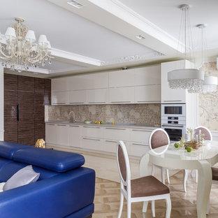 На фото: угловая кухня-гостиная в современном стиле с плоскими фасадами, белыми фасадами, светлым паркетным полом, бежевым полом и серой столешницей без острова