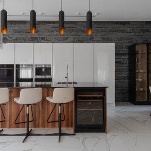 На фото: кухня-гостиная в современном стиле с островом, белым полом и черной столешницей