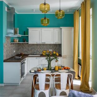 Идея дизайна: угловая кухня-гостиная в стиле современная классика с накладной раковиной, фасадами с утопленной филенкой, белыми фасадами, бежевым фартуком и серым полом без острова