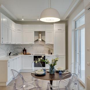 На фото: угловая кухня в стиле современная классика с накладной раковиной, фасадами с утопленной филенкой, белыми фасадами, белым фартуком, черной техникой, бежевым полом, обеденным столом и фартуком из мрамора без острова