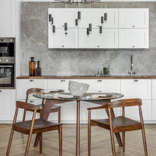 Идея дизайна: прямая кухня в современном стиле с накладной раковиной, фасадами в стиле шейкер, белыми фасадами, серым фартуком, техникой из нержавеющей стали, коричневым полом и коричневой столешницей без острова