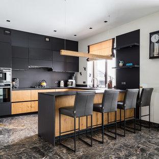 Неиссякаемый источник вдохновения для домашнего уюта: большая угловая кухня в современном стиле с обеденным столом, плоскими фасадами, столешницей из акрилового камня, черным фартуком, фартуком из каменной плиты, черной техникой, полом из керамогранита, полуостровом, коричневым полом, черной столешницей и черными фасадами