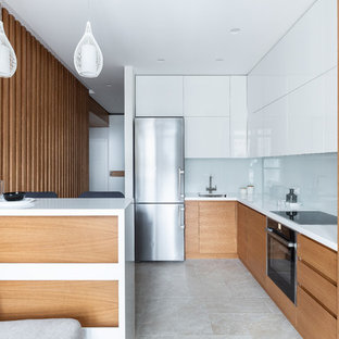 Photo of a mid-sized contemporary l-shaped separate kitchen in Saint Petersburg with an undermount sink, flat-panel cabinets, medium wood cabinets, solid surface benchtops, white splashback, glass tile splashback, porcelain floors, beige floor, white benchtop, black appliances and a peninsula.