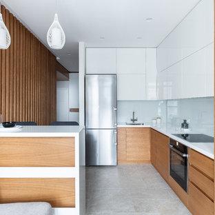 Идея дизайна: отдельная, угловая кухня среднего размера в современном стиле с врезной раковиной, плоскими фасадами, фасадами цвета дерева среднего тона, столешницей из акрилового камня, белым фартуком, фартуком из стеклянной плитки, полом из керамогранита, бежевым полом, белой столешницей, черной техникой и полуостровом