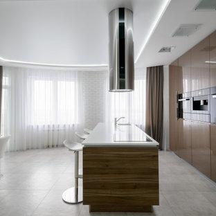 На фото: большая параллельная кухня в современном стиле с обеденным столом, монолитной раковиной, плоскими фасадами, коричневыми фасадами, техникой под мебельный фасад, полом из керамогранита, островом, серым полом и белой столешницей с