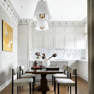 На фото: угловая кухня в стиле неоклассика (современная классика) с фасадами с утопленной филенкой, белыми фасадами, белым фартуком, островом, коричневым полом и белой столешницей
