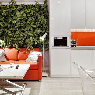 Ejemplo de cocina contemporánea con armarios con paneles lisos, puertas de armario blancas, electrodomésticos blancos, suelo de madera clara y salpicadero naranja