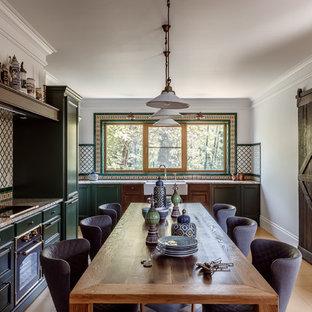 Пример оригинального дизайна: кухня в средиземноморском стиле с обеденным столом, раковиной в стиле кантри, фасадами с утопленной филенкой, зелеными фасадами и бежевым полом
