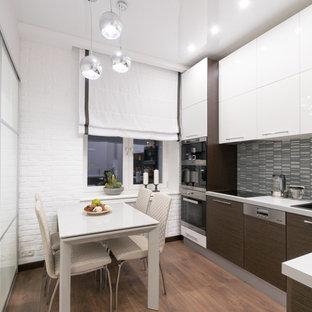Свежая идея для дизайна: отдельная, угловая кухня в современном стиле с накладной раковиной, плоскими фасадами, белыми фасадами, серым фартуком, техникой из нержавеющей стали, коричневым полом и белой столешницей без острова - отличное фото интерьера