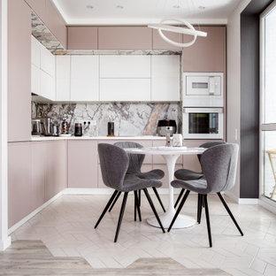 На фото: угловая кухня-гостиная в современном стиле с серым фартуком, белой техникой, белым полом, белой столешницей и многоуровневым потолком без острова с