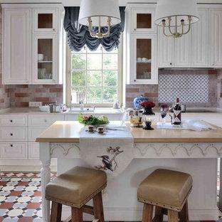 Новый формат декора квартиры: большая отдельная, п-образная кухня в классическом стиле с белыми фасадами, разноцветным фартуком, островом, врезной раковиной, фасадами с выступающей филенкой, мраморной столешницей, фартуком из терракотовой плитки, техникой из нержавеющей стали, полом из терракотовой плитки, разноцветным полом и бежевой столешницей