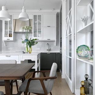 Свежая идея для дизайна: кухня в стиле современная классика с фасадами с утопленной филенкой, белыми фасадами, серым фартуком, паркетным полом среднего тона, островом, обеденным столом и коричневым полом - отличное фото интерьера