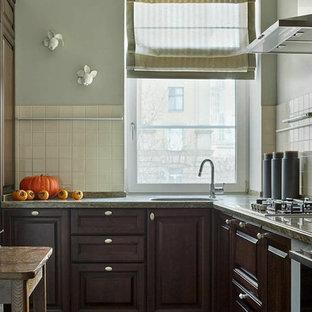 Новые идеи обустройства дома: угловая кухня в классическом стиле с фасадами с выступающей филенкой, темными деревянными фасадами, одинарной раковиной, белым фартуком и серым полом