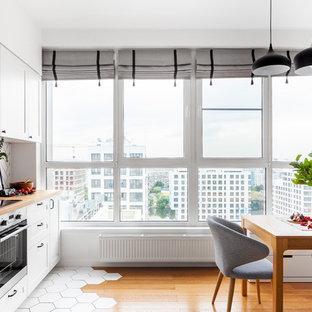 モスクワの北欧スタイルのおしゃれなI型キッチン (ドロップインシンク、木材カウンター、白いキッチンパネル、磁器タイルのキッチンパネル、セラミックタイルの床、アイランドなし、白い床) の写真