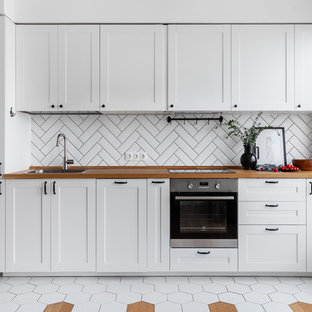 Inspiration for a scandinavian single-wall kitchen in Moscow with shaker cabinets, white cabinets, white splashback, stainless steel appliances, no island, a single-bowl sink, wood benchtops and multi-coloured floor.