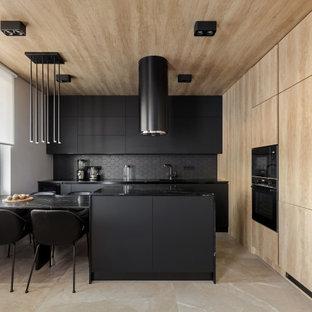 На фото: угловая кухня в современном стиле с плоскими фасадами, черными фасадами, черным фартуком, черной техникой, полуостровом, бежевым полом, черной столешницей и деревянным потолком