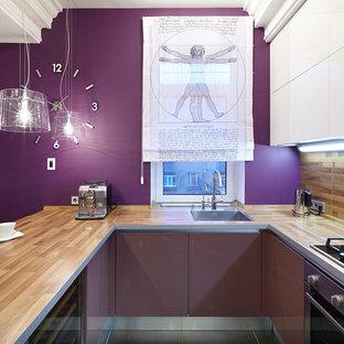 Foto de cocina en U, actual, abierta, con fregadero encastrado, armarios con paneles lisos, salpicadero marrón, electrodomésticos de acero inoxidable y península