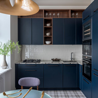 На фото: угловая кухня в стиле современная классика с обеденным столом, врезной раковиной, синими фасадами, белым фартуком, черной техникой, белой столешницей, фасадами с декоративным кантом и серым полом без острова с