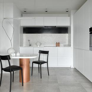 Удачное сочетание для дизайна помещения: угловая кухня среднего размера в современном стиле с обеденным столом, врезной раковиной, плоскими фасадами, белыми фасадами, белым фартуком, фартуком из плитки мозаики, черной техникой, серым полом и белой столешницей без острова - самое интересное для вас