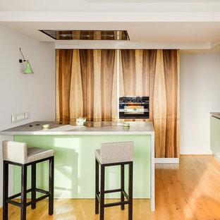 На фото: кухня в современном стиле с накладной раковиной, плоскими фасадами, зелеными фасадами, столешницей из бетона, черной техникой, паркетным полом среднего тона, островом, коричневым полом и серой столешницей