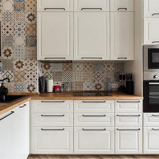 Идея дизайна: угловая кухня в классическом стиле с накладной раковиной, фасадами с выступающей филенкой, белыми фасадами, деревянной столешницей и разноцветным фартуком