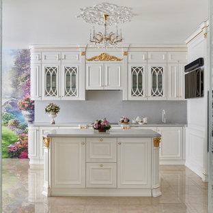 Пример оригинального дизайна интерьера: большая угловая кухня в классическом стиле с обеденным столом, врезной раковиной, фасадами с выступающей филенкой, белыми фасадами, мраморной столешницей, белым фартуком, фартуком из мрамора, черной техникой, мраморным полом, островом и бежевым полом