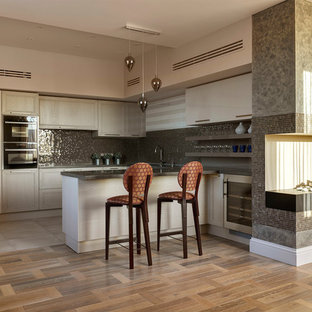 Photo of an expansive transitional u-shaped open plan kitchen in Moscow with an undermount sink, raised-panel cabinets, beige cabinets, marble benchtops, grey splashback, mosaic tile splashback, black appliances, medium hardwood floors, a peninsula and brown floor.