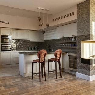 Неиссякаемый источник вдохновения для домашнего уюта: огромная п-образная кухня-гостиная в стиле современная классика с врезной раковиной, фасадами с выступающей филенкой, бежевыми фасадами, мраморной столешницей, серым фартуком, фартуком из плитки мозаики, черной техникой, паркетным полом среднего тона, полуостровом и коричневым полом