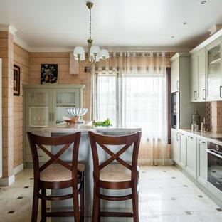 На фото: параллельная кухня в стиле кантри с фасадами с утопленной филенкой, зелеными фасадами, разноцветным фартуком, техникой из нержавеющей стали, островом, бежевым полом и бежевой столешницей