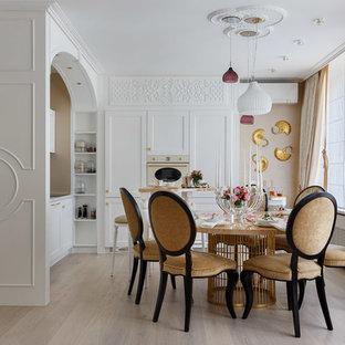 Выдающиеся фото от архитекторов и дизайнеров интерьера: угловая кухня-гостиная в стиле современная классика с белыми фасадами, белой техникой, светлым паркетным полом и бежевым полом без острова
