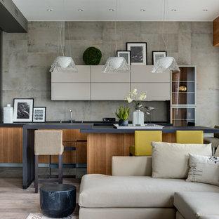 На фото: большая угловая кухня-гостиная в современном стиле с врезной раковиной, плоскими фасадами, фасадами цвета дерева среднего тона, столешницей из кварцевого агломерата, серым фартуком, фартуком из керамогранитной плитки, черной техникой, полом из керамогранита, островом и серым полом с