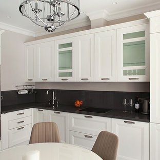Пример оригинального дизайна: угловая кухня в стиле современная классика с фасадами с утопленной филенкой, белыми фасадами, черным фартуком, техникой из нержавеющей стали, черной столешницей, обеденным столом и одинарной раковиной без острова