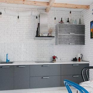 Идея дизайна: угловая кухня-гостиная в современном стиле с накладной раковиной, плоскими фасадами, серыми фасадами, белым фартуком, фартуком из стекла, техникой из нержавеющей стали, деревянным полом и белым полом без острова