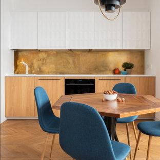 Свежая идея для дизайна: маленькая линейная кухня в современном стиле с обеденным столом, плоскими фасадами, фасадами цвета дерева среднего тона, фартуком цвета металлик, черной техникой, паркетным полом среднего тона, коричневым полом и белой столешницей без острова - отличное фото интерьера