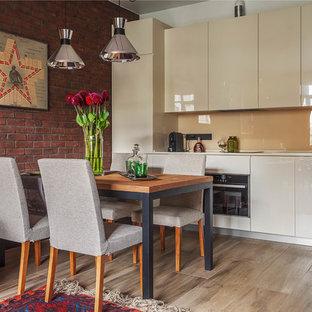 Идея дизайна: линейная кухня-гостиная в современном стиле с плоскими фасадами, бежевыми фасадами, бежевым фартуком, фартуком из стекла, черной техникой, бежевым полом и паркетным полом среднего тона без острова