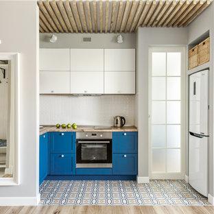 Свежая идея для дизайна: п-образная кухня-гостиная в скандинавском стиле с накладной раковиной, фасадами в стиле шейкер, синими фасадами, деревянной столешницей, белым фартуком, разноцветным полом, коричневой столешницей и белой техникой без острова - отличное фото интерьера