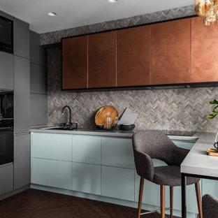 Неиссякаемый источник вдохновения для домашнего уюта: маленькая п-образная кухня в современном стиле с обеденным столом, одинарной раковиной, плоскими фасадами, столешницей из акрилового камня, разноцветным фартуком, фартуком из плитки мозаики, черной техникой, полом из винила, полуостровом, бежевым полом, серой столешницей и синими фасадами