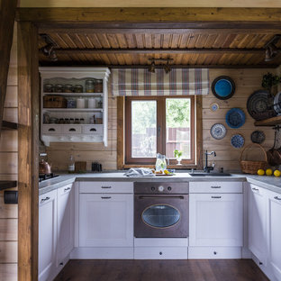 Photo of a mid-sized country u-shaped open plan kitchen in Moscow with an undermount sink, beaded inset cabinets, white cabinets, concrete benchtops, beige splashback, timber splashback, coloured appliances, dark hardwood floors, no island, brown floor and grey benchtop.