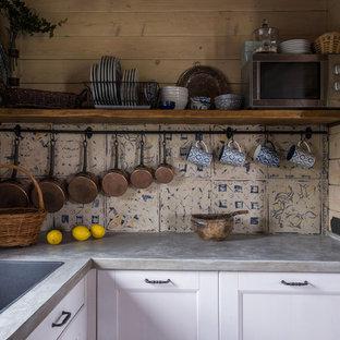 На фото: отдельная, п-образная кухня среднего размера в стиле рустика с врезной раковиной, белыми фасадами, столешницей из бетона, серым фартуком, фартуком из дерева, серой столешницей и фасадами с утопленной филенкой без острова с
