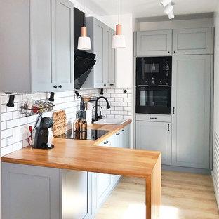 モスクワのコンテンポラリースタイルのおしゃれなL型キッチン (ドロップインシンク、落し込みパネル扉のキャビネット、グレーのキャビネット、木材カウンター、白いキッチンパネル、黒い調理設備、アイランドなし、茶色い床、茶色いキッチンカウンター) の写真