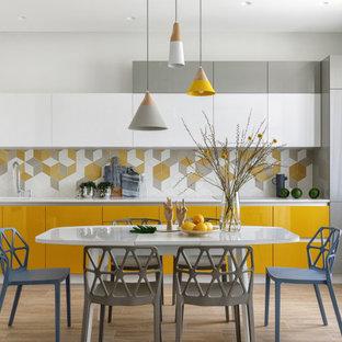 Пример оригинального дизайна: линейная кухня среднего размера в скандинавском стиле с обеденным столом, врезной раковиной, плоскими фасадами, желтыми фасадами, столешницей из кварцевого агломерата, желтым фартуком, фартуком из керамической плитки, белой техникой, полом из керамогранита, бежевым полом и белой столешницей без острова