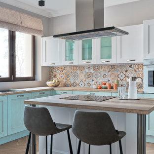 Идея дизайна: отдельная, угловая кухня в современном стиле с накладной раковиной, фасадами с утопленной филенкой, бирюзовыми фасадами, разноцветным фартуком, цветной техникой, островом, коричневым полом и бежевой столешницей