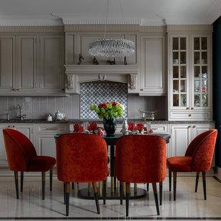 На фото: кухни в стиле современная классика с обеденным столом, фасадами с выступающей филенкой, серым фартуком, бежевым полом, бежевыми фасадами и коричневой столешницей без острова
