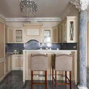 Стильный дизайн: п-образная кухня в классическом стиле с фасадами с выступающей филенкой, бежевыми фасадами, серым фартуком, техникой под мебельный фасад, полуостровом, серым полом и бежевой столешницей - последний тренд