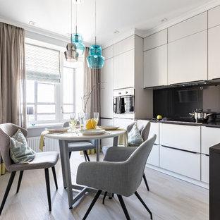 Свежая идея для дизайна: угловая кухня среднего размера в современном стиле с врезной раковиной, плоскими фасадами, серыми фасадами, черным фартуком, бежевым полом и черной столешницей - отличное фото интерьера