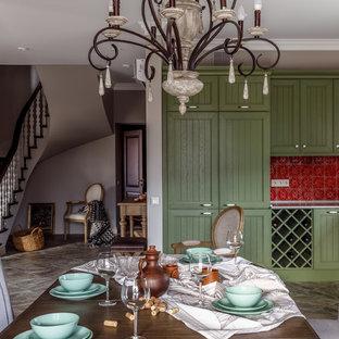 Стильный дизайн: угловая кухня-гостиная в стиле кантри с фасадами с утопленной филенкой, зелеными фасадами, красным фартуком, серым полом, белой столешницей, фартуком из керамической плитки и техникой под мебельный фасад без острова - последний тренд